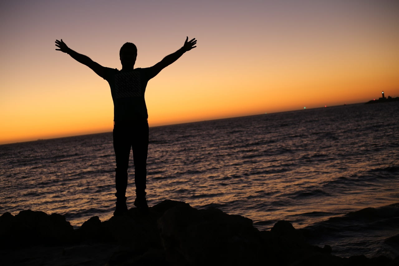 man standing on rocks at sunset