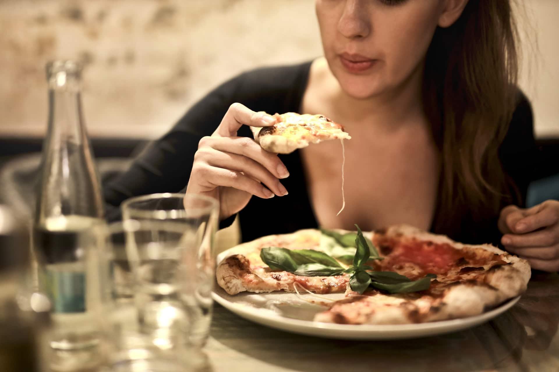 woman eating flatbread pizza
