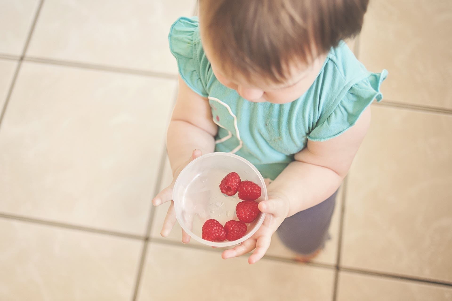 baby holding bowl of raspberries